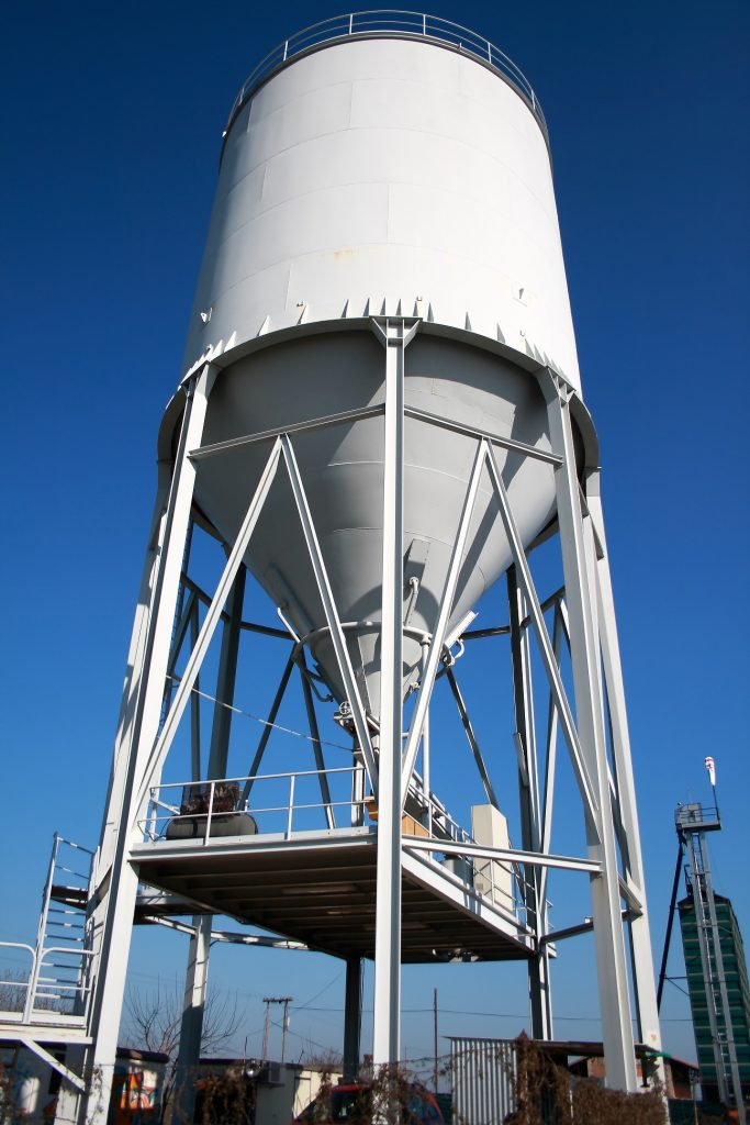 a wide shot of a large scale white metal water tank