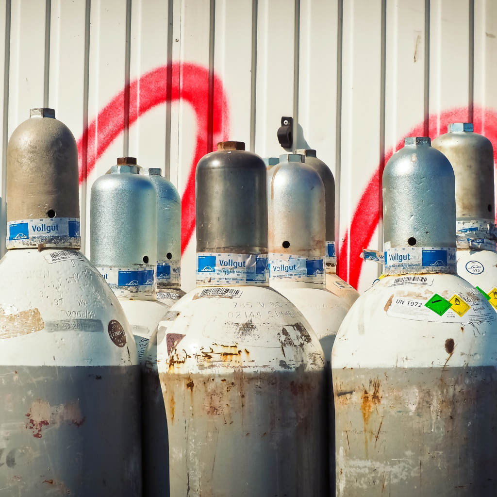 a group of nitrogen gas canisters lined up in front of corrugated iron