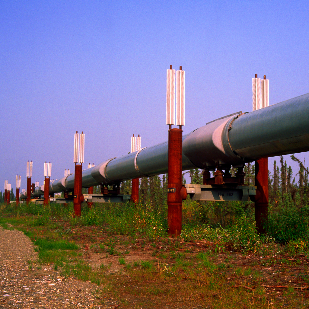 red and silver oil pipeline that is running through a field of dry fields