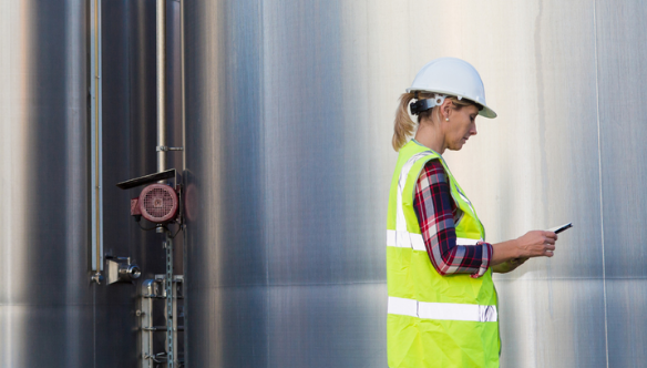a female engineer in a high vis jacket and a hard hart in front of a large silver tank performing health and safety assessments
